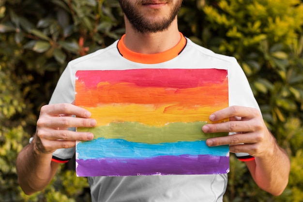 Vista frontal individual segurando arco-íris de papel colorido