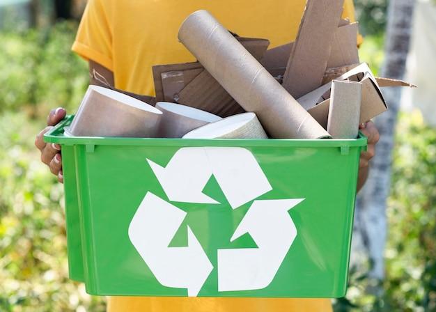 Vista frontal individual segurando produtos reciclados