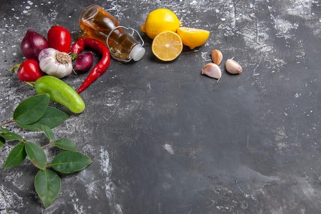 Vista frontal, ingredientes frescos, óleo, alho, fatias de limão e outros produtos
