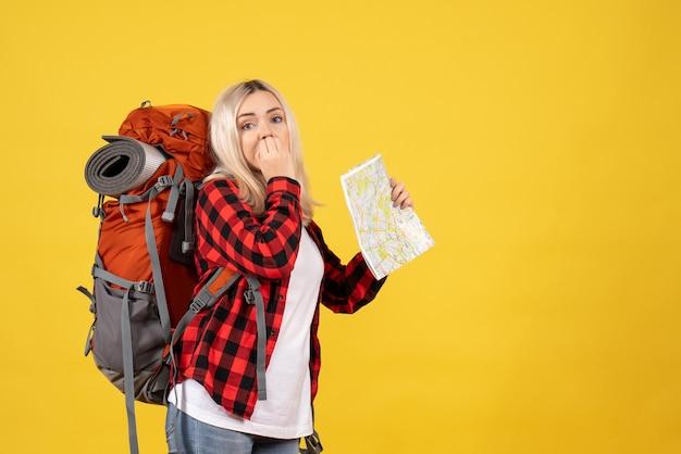 Vista frontal intrigada garota viajante com sua mochila segurando o mapa