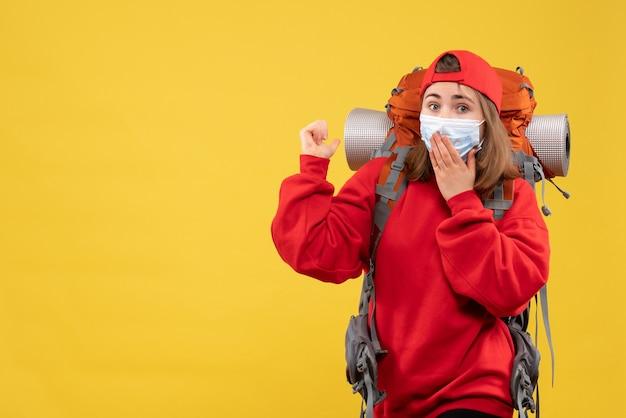 Vista frontal intrigada turista feminina com mochila e máscara apontando para trás