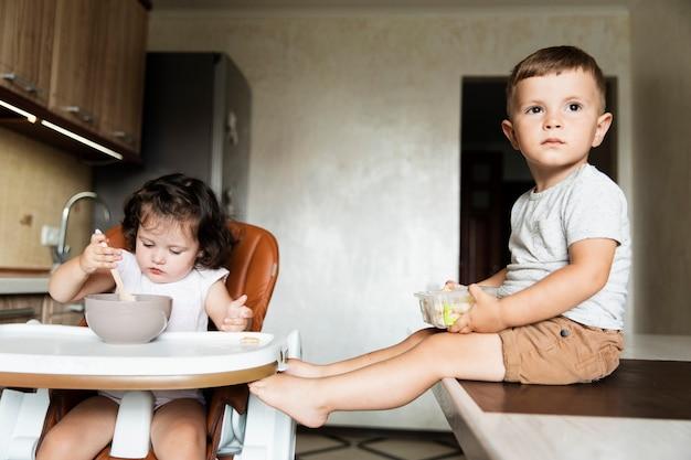 Vista frontal irmãos bonitos na cozinha