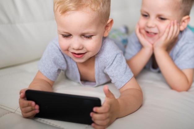 Vista frontal irmãos jogando no smartphone