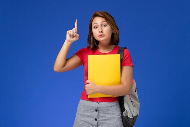 Vista frontal jovem aluna de camisa vermelha com mochila segurando arquivos amarelos com o dedo levantado sobre fundo azul.