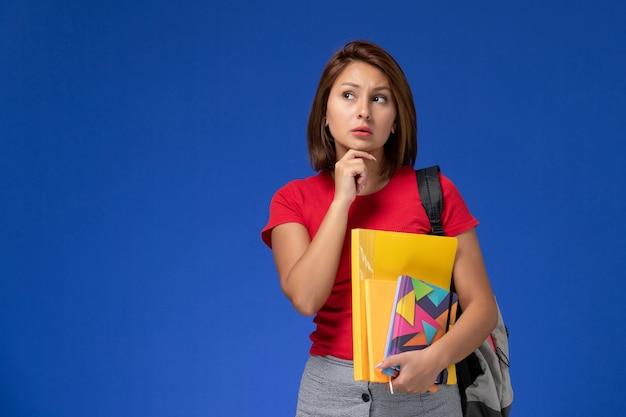 Vista frontal jovem aluna de camisa vermelha, usando mochila segurando arquivos e caderno pensando sobre o fundo azul.