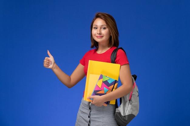Vista frontal jovem aluna de camisa vermelha, usando mochila segurando arquivos e o caderno sobre o fundo azul.