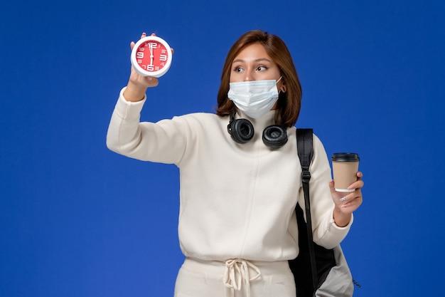 Vista frontal jovem aluna em camisa branca usando máscara e mochila segurando o relógio com café na parede azul