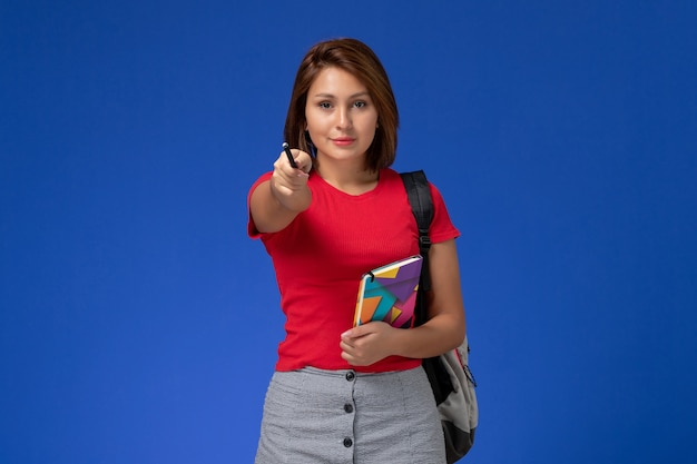 Vista frontal jovem aluna em camisa vermelha, usando mochila segurando o caderno com caneta sobre fundo azul claro.