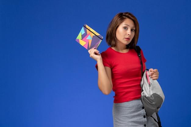 Vista frontal jovem aluna em camisa vermelha, usando mochila segurando o caderno sobre fundo azul claro.