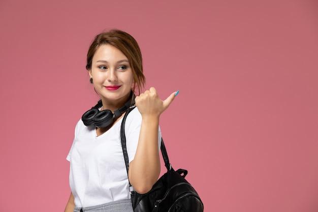 Vista frontal, jovem aluna em camiseta branca e calça cinza sorrindo, posando e pensando expressão na mesa rosa aulas de faculdade universitária