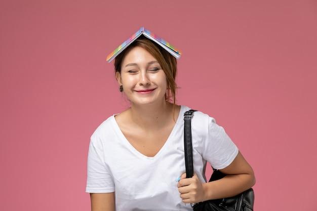 Vista frontal jovem aluna em camiseta branca sorrindo segurando bolsa no fundo rosa lição livro de estudo da faculdade da universidade