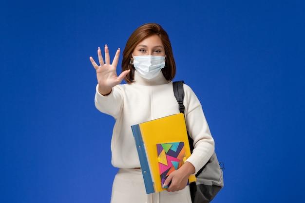 Vista frontal, jovem aluna em jérsei branco usando máscara com bolsa e cadernos na mesa azul aulas