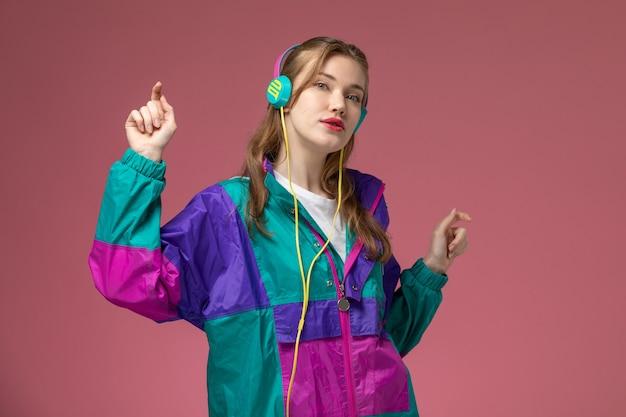 Vista frontal jovem atraente feminino ouvindo música em um casaco colorido com passos de dança na parede rosa modelo cor feminino jovem