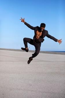 Vista frontal jovem bl ck m vestindo roupas casuais pulando.