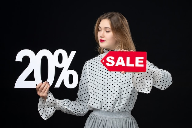 Vista frontal jovem bonita feminina segurando a escrita da venda e no fundo preto modelo emoção compras beleza cor moda