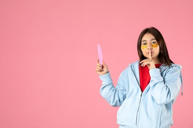 Vista frontal jovem, bonita, mulher com tapa-olho e lixa de unha no fundo rosa
