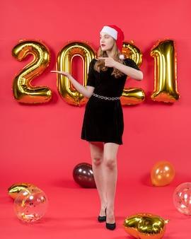 Vista frontal, jovem, bonita, mulher, em, vestido preto, balões, apontando para algo, vermelho