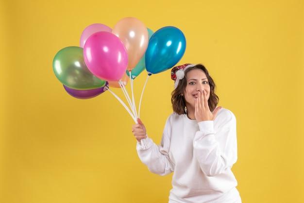 Vista frontal, jovem, bonita, mulher, segurando, balões, amarela, ano novo, emoções, natal, cor mulher