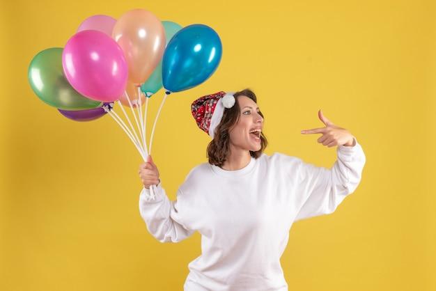 Vista frontal, jovem, bonita, mulher, segurando, balões, amarela, mulher natal, cor, emoção