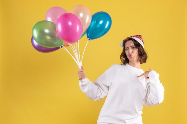 Vista frontal, jovem, bonita, mulher, segurando, balões, amarela, natal, ano novo, cor mulher, emoção