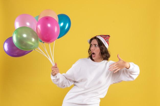 Vista frontal, jovem, bonita, mulher, segurando, balões coloridos, amarela, novo, ano, emoção, natal, mulher, cor