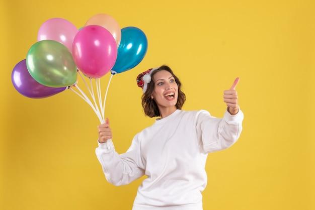 Vista frontal, jovem, bonita, mulher, segurando, balões coloridos, em, amarela, emoção