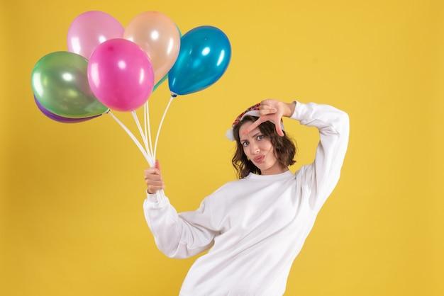 Vista frontal, jovem, bonita, mulher, segurando, balões, ligado, amarela, natal, mulher, cor, ano, emoções, cor