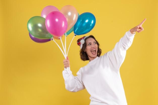 Vista frontal, jovem, bonita, mulher, segurando, balões, natal, amarela, ano novo, cor