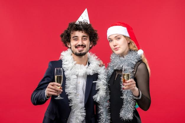 Vista frontal jovem casal comemorando ano novo em feriados de parede vermelha amor de natal