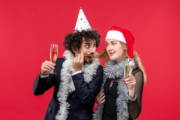 Vista frontal jovem casal comemorando ano novo na festa de amor de natal na parede vermelha