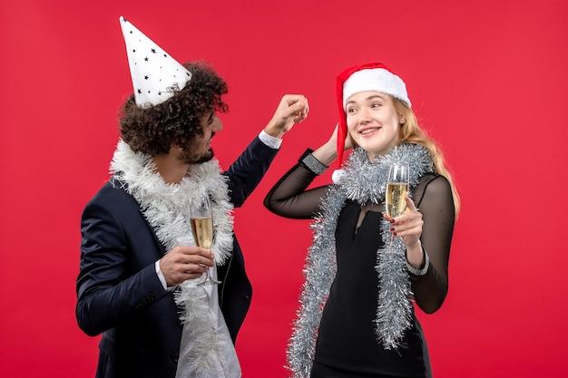 Vista frontal jovem casal comemorando ano novo na festa de parede vermelha ama o natal