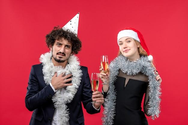 Vista frontal jovem casal comemorando ano novo na festa de parede vermelha amor de natal