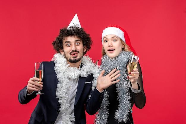 Vista frontal jovem casal comemorando ano novo na parede vermelha feriados natal amor