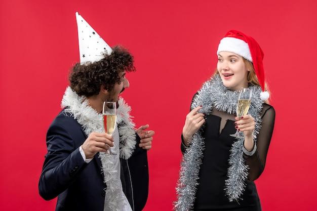 Vista frontal jovem casal comemorando ano novo na parede vermelha festa feriado natal amor