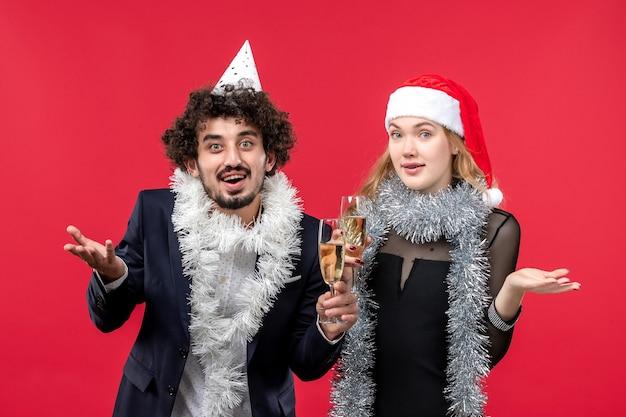 Vista frontal jovem casal comemorando ano novo no amor de natal de parede vermelha