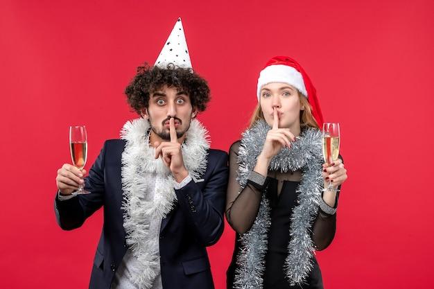 Vista frontal jovem casal comemorando ano novo no piso vermelho ama festa de natal