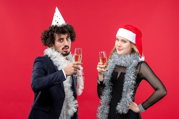 Vista frontal jovem casal feliz comemorando ano novo na parede vermelha férias natal amor