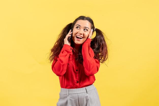 Vista frontal jovem com blusa vermelha com cabelo bonito falando ao telefone no fundo amarelo cor de fundo amarelo criança menina criança juventude inocência