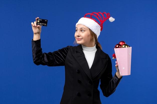 Vista frontal jovem com brinquedos de árvore e cartão do banco na parede azul, feriado de ano novo