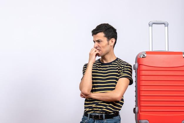 Vista frontal jovem com camiseta listrada e mala vermelha pensando