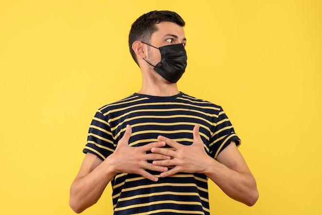 Vista frontal jovem com camiseta listrada em preto e branco colocando a mão no fundo amarelo do peito