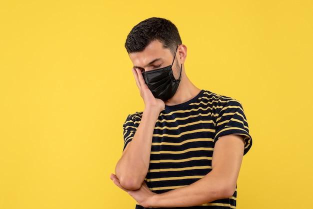 Vista frontal jovem com camiseta listrada em preto e branco colocando a mão no rosto fundo amarelo