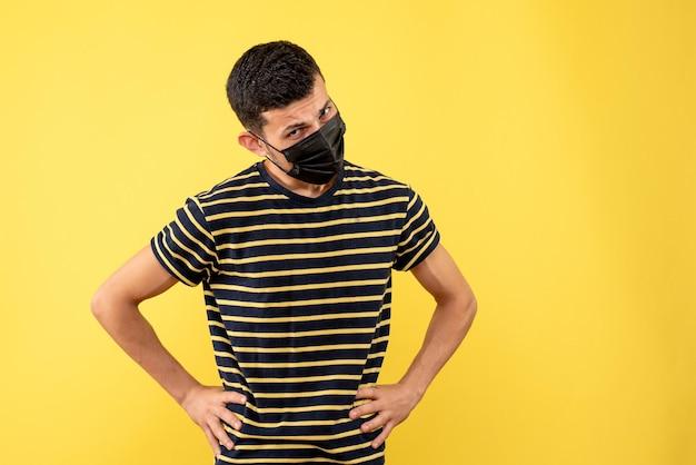 Vista frontal jovem com camiseta listrada em preto e branco colocando as mãos em um fundo amarelo de cintura