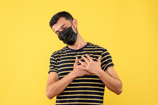 Vista frontal jovem com camiseta listrada em preto e branco colocando as mãos no peito fundo amarelo