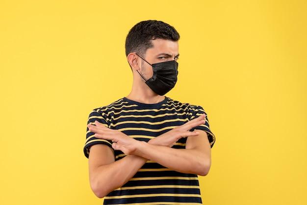 Vista frontal jovem com camiseta listrada em preto e branco, cruzando as mãos no fundo amarelo