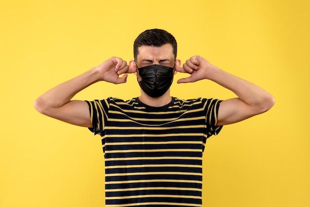 Vista frontal jovem com camiseta listrada em preto e branco fechando as orelhas no fundo amarelo