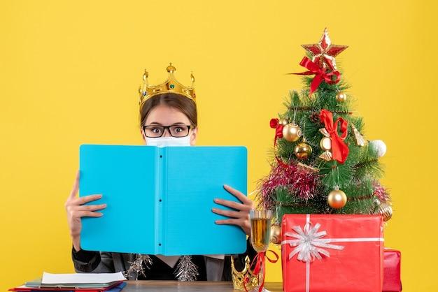 Vista frontal jovem com coroa cobrindo o rosto com pasta de papel azul árvore de natal e coquetel de presentes