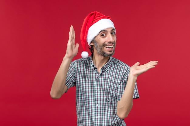 Vista frontal jovem com expressão animada na parede vermelha feriados ano novo masculino vermelho