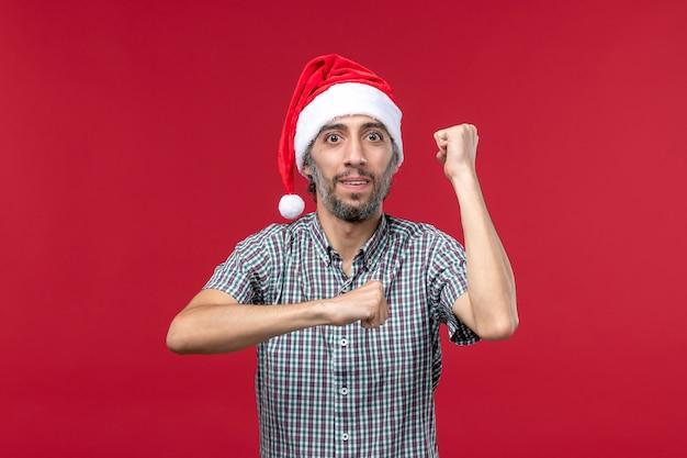Vista frontal jovem com expressão animada na parede vermelha homem vermelho feriado de ano novo