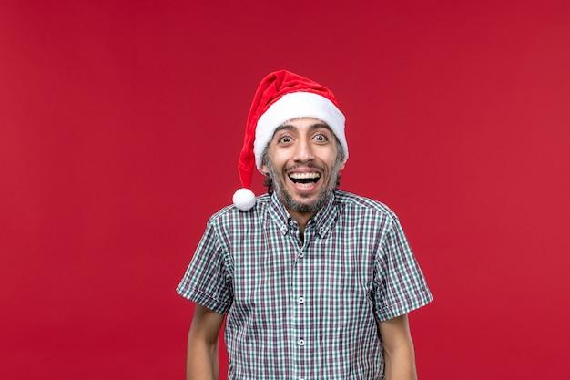 Vista frontal jovem com expressão sorridente na parede vermelha feriado vermelho ano novo